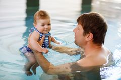 Happy middle-aged father swimming with cute adorable baby daughter in whirl pool. Smiling dad and little child, girl of royalty free stock image