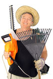 Happy Middle Aged Gardener. Carrying an array of gardening tools Royalty Free Stock Image