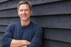 Happy Middle Aged Man Arms Folded. Portrait shot of an attractive, successful and happy middle aged man male arms folded outside wearing a blue sweater royalty free stock image
