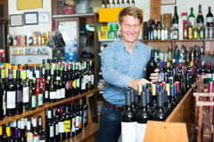 Happy middle-aged man customer buying bottle of wine Royalty Free Stock Photos