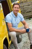Happy Middle Aged Man Drinking Tea or Coffee Sitting In Van. Portrait shot of an attractive, successful and happy middle aged man male wearing a blue polo shirt stock photos