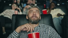 Happy middle-aged man is laughing eating popcorn watching movie in cinema stock video