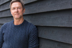 Happy Middle Aged Man Outside. Portrait shot of an attractive, successful and happy middle aged man male outside wearing a blue sweater Royalty Free Stock Image