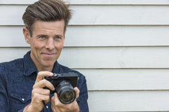 Happy Middle Aged Man Photographer Using Camera. Portrait shot of an attractive, successful and happy middle aged man male photographer outside taking Royalty Free Stock Photo