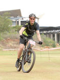 Happy middle aged man riding to the finish line at Mountain Bike Stock Photography