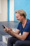 Happy middle aged man sitting on steps using mobile phone Royalty Free Stock Photos