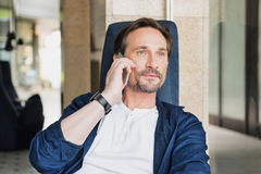 Happy middle-aged man talking on mobile phone. Waist up portrait of positive businessman communicating on cellphone while resting in cafe. He is gently smile Royalty Free Stock Photography