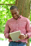 Happy middle aged man using tablet in park Stock Photos