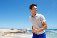 Happy middle aged man walking on the beach Stock Images