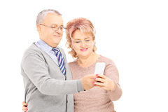 Happy middle aged man and woman looking at mobile phone Stock Photos