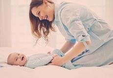 Happy middle aged mother with her child in a bed. Beautiful middle aged mother with her child in a bed royalty free stock photography