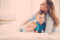 Happy middle aged mother with her children in a bed. Beautiful middle aged mother with her child in a bed royalty free stock image
