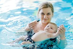 Happy middle-aged mother swimming with cute adorable baby in swimming pool. Smiling mom and little child, newborn girl having fun together. Active family Stock Photos