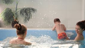 Happy middle-aged mother swimming with cute adorable baby in swimming pool. Smiling mom and little child, newborn girl. Having fun together. Active family stock video
