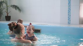 Happy middle-aged mother swimming with cute adorable baby in swimming pool. Smiling mom and little child, newborn girl. Having fun together. Active family stock video footage