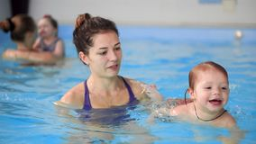 Happy middle-aged mother swimming with cute adorable baby in swimming pool. Smiling mom and little child, newborn girl. Having fun together. Active family stock footage