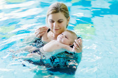 Happy middle-aged mother swimming with cute adorable baby in swimming pool. Smiling mom and little child, newborn girl having fun together. Active family Royalty Free Stock Photography