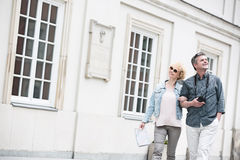 Happy middle-aged tourist couple walking arm in arm by building Royalty Free Stock Photo