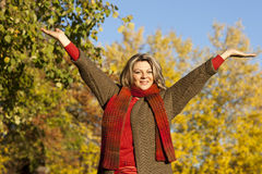 Happy middle aged woman with arms outstretched stock images