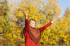 Happy middle aged woman with arms outstretched Stock Photo