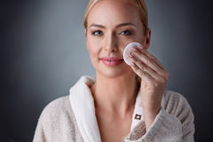Happy middle aged woman cleaning face and removing make up with. Cotton pad, beauty, people and skincare concept stock image