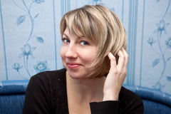 Happy middle aged woman correcting hair. stock image
