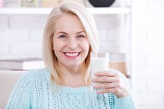 Happy middle aged woman drinking milk Royalty Free Stock Photography