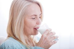 Happy middle aged woman drinking milk Stock Images