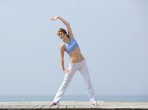 Happy middle aged woman exercising at beach Royalty Free Stock Images