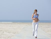 Happy middle aged woman jogging. Full length portrait of a happy middle aged woman jogging at the beach royalty free stock photos