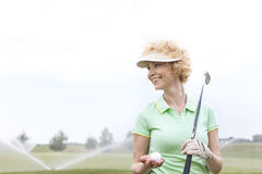 Happy middle-aged woman looking away while holding golf club and ball. Happy middle-aged women looking away while holding golf club and ball royalty free stock image