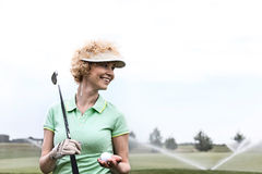 Happy middle-aged woman looking away while holding golf club and ball. Happy middle-aged women looking away while holding golf club and ball stock photo