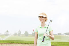 Happy middle-aged woman looking away while holding golf club. Happy middle-aged women looking away while holding golf club royalty free stock photo