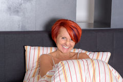Happy Middle Aged Woman lying in the Bed Stock Images