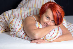 Happy Middle Aged Woman lying in the Bed. Stock Photo