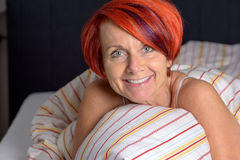 Happy Middle Aged Woman lying in the Bed. Royalty Free Stock Images