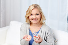 Happy middle aged woman with medicine at home Stock Photo