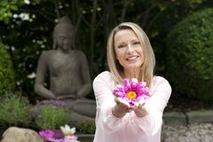 Happy middle aged woman offers flowers in zen garden. Smiling royalty free stock photo