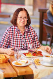 Happy middle aged woman in a restaurant Royalty Free Stock Photography