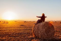 Happy middle-aged woman sitting on haystack in autumn field and feeling free with arms opened. Relaxing and admiring nature at sunset stock photography