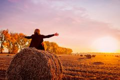 Happy middle-aged woman sitting on haystack in autumn field and feeling free with arms opened stock image