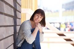 Happy middle aged woman sitting outside Royalty Free Stock Images