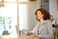 Happy middle aged woman using laptop at home Royalty Free Stock Image