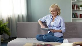 Happy middle-aged woman viewing funny videos on tablet, sitting on couch at home. Stock photo stock photos
