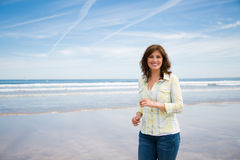Happy middle aged woman walking on the beach Stock Photography