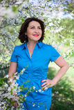 Happy middle aged woman walking in blooming garden Stock Image