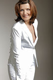 Happy middle-aged woman in white suit. Royalty Free Stock Images