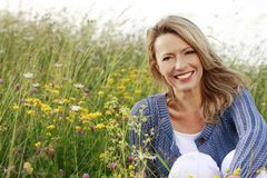 Happy middle aged woman in wild flower field. Smiling Stock Photos