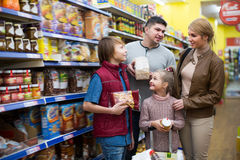 Happy middle-class family purchasing food. Happy middle-class family of four purchasing food in shop together Stock Photos