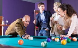 Happy middle class people having pool game. In billiard club Royalty Free Stock Photos